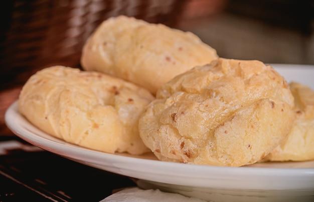 Comida brasileira pão de queijo servido em um prato branco na foto do close up