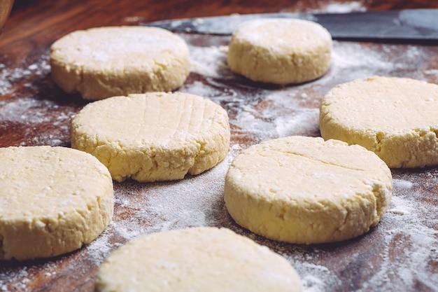 Comida caseira e comida. panquecas de queijo cottage em cru. panquecas tradicionais de queijo cottage no café da manhã na rússia, ucrânia e europa.