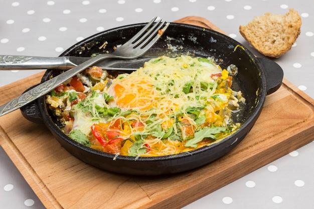 Comida caseira, faca e garfo, ralador de queijo com azeitonas na mesa
