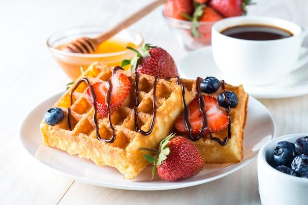 Comida caseira fresca de waffles belgas com mel, chocolate, morango, mirtilo, xarope de bordo e creme. conceito de pequeno-almoço saudável sobremesa com suco