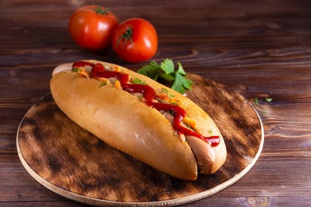 Comida caseira hotdog recheado com linguiça e legumes na madeira