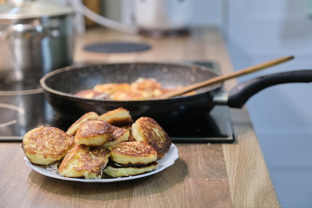 Comida caseira, o processo de fritar em uma panela de cheesecakes, panquecas de requeijão, cozinha caseira