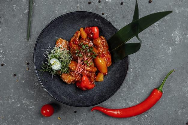 Comida chinesa de frango cantonês. consiste em frango, pimentão, abacaxi, molho picante doce à base de purê de lichia.