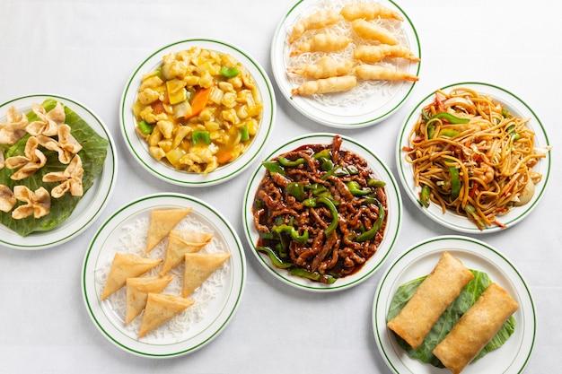 Comida chinesa em uma mesa de toalha de mesa branca. carne com molho de alho, frango ao curry, rolinhos primavera, macarrão com legumes, camarão com camarão.