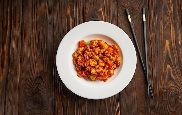 Comida chinesa, frango kung pao em prato branco com pauzinhos na mesa de madeira, vista de cima e espaço de cópia