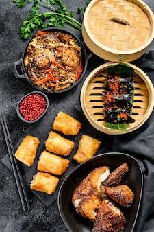 Comida chinesa. macarrão, bolinhos, frango frito, dim sum, rolinhos primavera. conjunto de cozinha chinesa. vista do topo