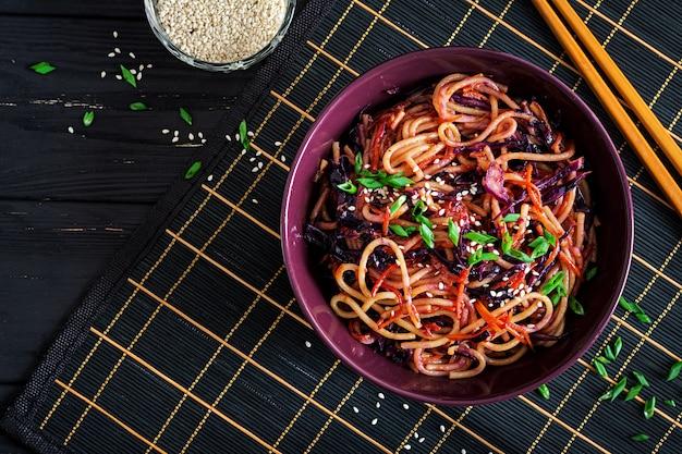Comida chinesa. macarrão frito de vegan com couve roxa e cenoura em uma tigela sobre um fundo preto de madeira.