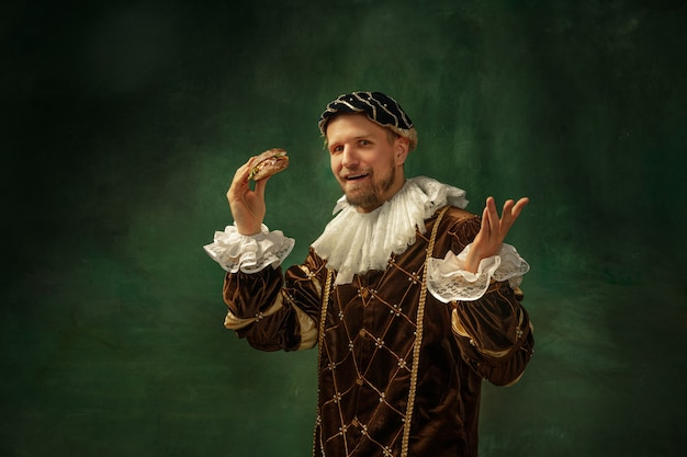 Comida chocante. retrato de jovem medieval em roupas vintage, com moldura de madeira em fundo escuro. modelo masculino como duque, príncipe, pessoa real. conceito de comparação de eras, moderno, moda.