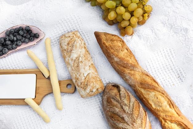 Comida colocada no cobertor de piquenique. pão fresco, uvas e photocam leigos sobre manta branca
