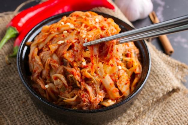 Comida coreana, kimchi de repolho no prato preto.