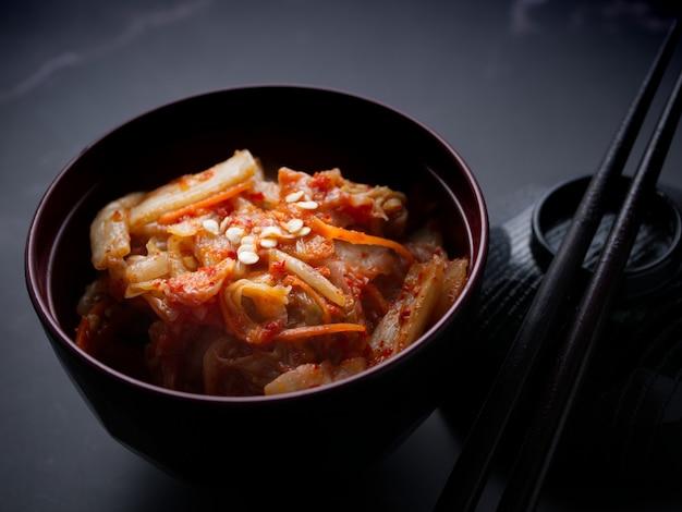 Comida coreana, repolho kimchi em prato preto em fundo escuro.