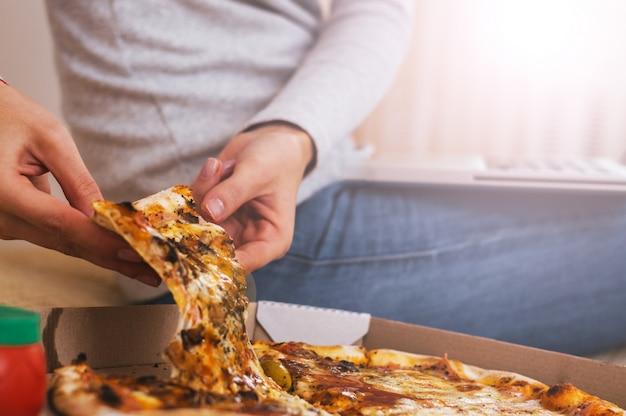 Comida, cozinha italiana e comer conceito - close-up de mão tomando e pizza