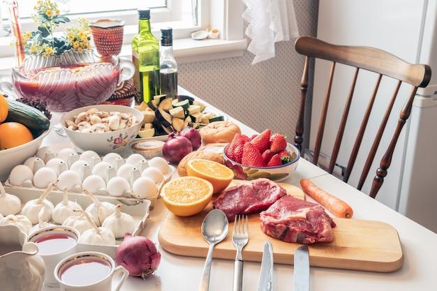 Comida crua de ingredientes com legumes e frutas, preparando-se para cozinhar na mesa