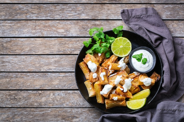 Comida da culinária brasileira, lanche latino. mandioca frita, mandioca, mandioca, palitos de manioca com molho de coentro. vista superior do plano de fundo