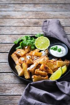 Comida da culinária brasileira, lanche latino. mandioca frita, mandioca, mandioca, palitos de manioca com molho de coentro.