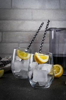Comida da moda. bebidas de verão. conceito de dieta de desintoxicação. ingredientes para a limonada preta com carvão, gelo, suco de limão e limão.