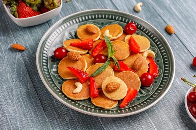 Comida da moda - cereal mini panqueca. pilha de panquecas de cereais com frutas e nozes.