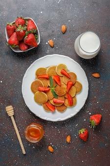 Comida da moda - cereal mini panqueca. pilha de panquecas de cereais com frutas