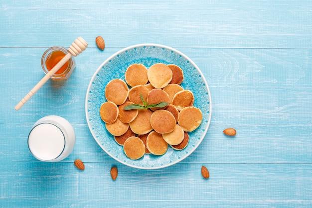 Comida da moda - mini cereal panqueca. pilha de panquecas de cereais com frutas e nozes.