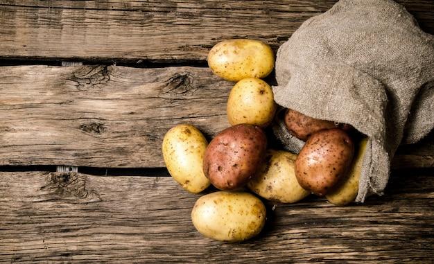 Comida de batata crua. batatas frescas em um velho saco com fundo de madeira. lugar livre para texto.