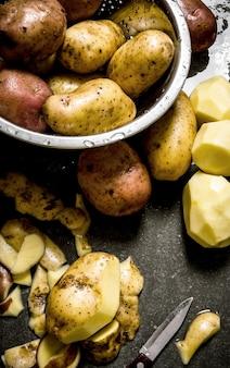 Comida de batata. o conceito de batatas descascadas molhadas na mesa de pedra.