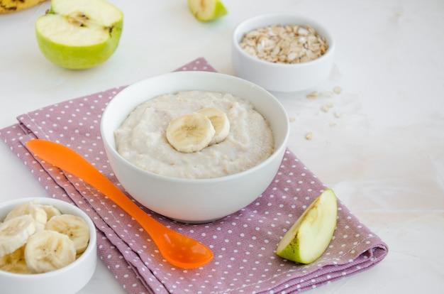 Comida de bêbe. aveia cremosa com fatias de banana e maçã em uma tigela com uma colher sobre um fundo claro. café da manhã saudável.