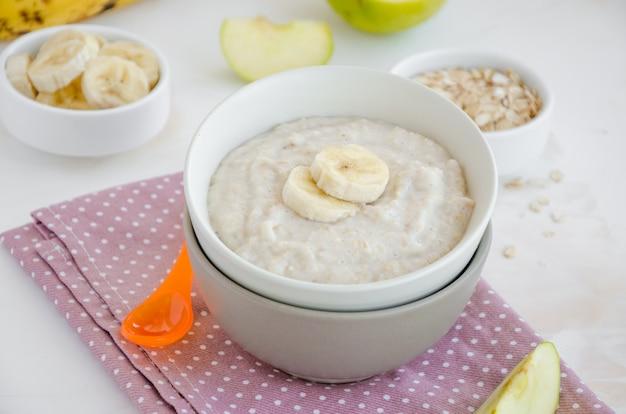 Comida de bêbe. aveia cremosa com fatias de banana e maçã em uma tigela mingau no café da manhã.