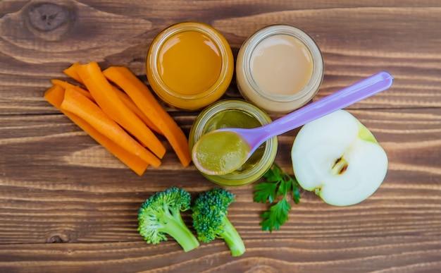 Comida de bêbe. purê de legumes e frutas em potes. foco seletivo.