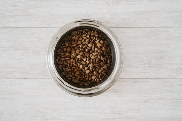 Comida de cachorro ração seca em tigela no chão