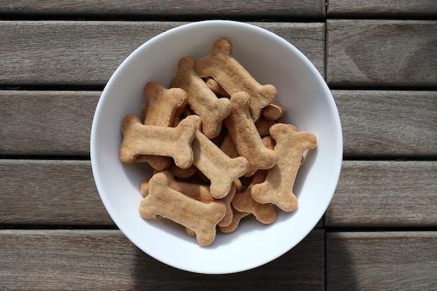 Comida de cachorro seca em uma tigela na vista superior do plano de fundo de madeira.