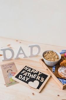 Comida de café da manhã e saudação perto de desenho e escrita do pai