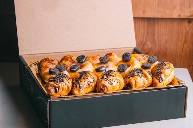 Comida de croissants e donuts de chocolate entrega lanches doces em uma caixa