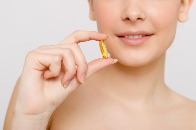 Comida de dieta saudável. bela jovem sorridente segurando um comprimido de óleo de peixe na mão. fechar-se. tomar cápsula. suplementos vitamínicos e dietéticos