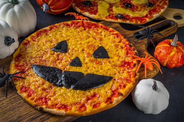 Comida de doces ou travessuras para festa de halloween, pizza assustadora engraçada no estilo dos personagens de halloween - morcegos, aranhas, abóbora jack o lantern, cheddar, mussarela e queijo preto