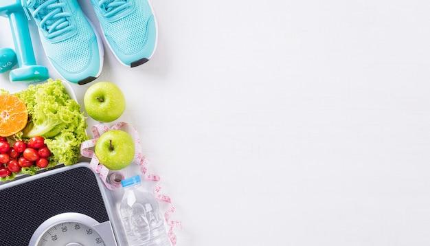 Comida de estilo de vida saudável e conceito de esporte em fundo branco de madeira