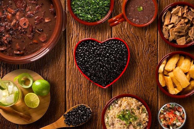 Comida de feijoada brasileira. vista superior com pote de feijão de coração vermelho.