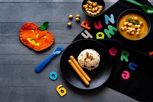 Comida de festa de halloween para crianças com risoto de abóbora e salsichas, papel de parede de fundo