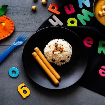 Comida de festa de halloween para crianças com risoto de abóbora e salsichas