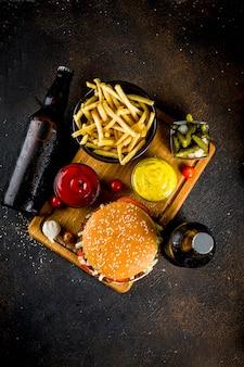 Comida de festa, hambúrgueres, batatas fritas, batatas fritas, pepinos em conserva, cebola, tomate e garrafas de cerveja gelada