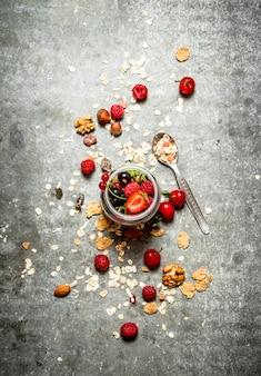 Comida de fitness. bagas com muesli e nozes na mesa de pedra.
