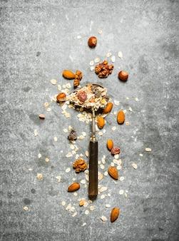 Comida de fitness. cereais e frutas secas em colher na mesa de pedra.