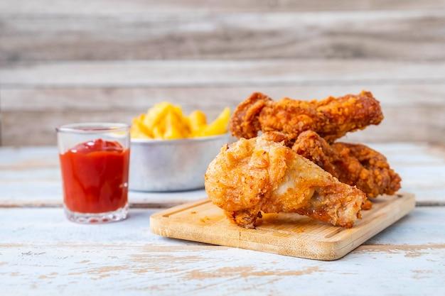 Comida de frango frito e batatas fritas em uma mesa de madeira