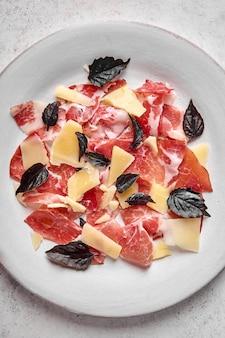 Comida de fundo prosciutto coppa di parma fatias de presunto com queijo parmesão e manjericão escuro na luz