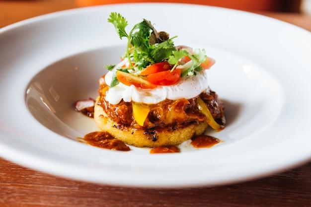 Comida de fusão: cobertura de canapé de hambúrguer com ovo, tomate e coentro.
