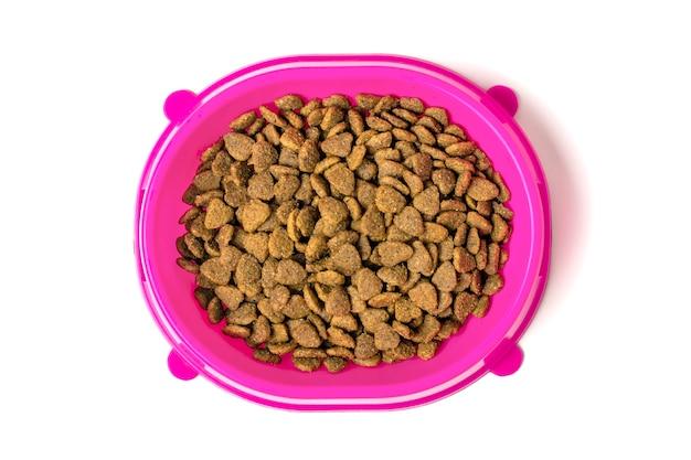 Comida de gato seca em tigela de plástico rosa isolada