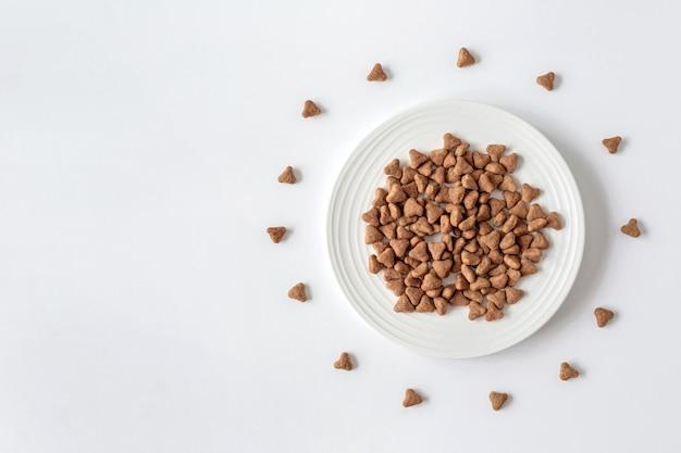 Comida de gato seca em uma tigela branca sobre um fundo branco. a vista do topo