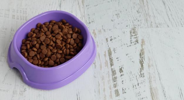 Comida de gato seca no prato roxo em uma mesa branca
