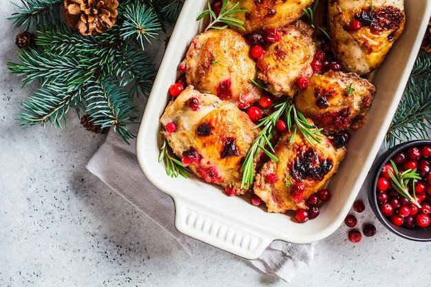 Comida de natal, carne de frango assado com cranberries e alecrim no prato do forno, superfície branca, espaço da cópia,