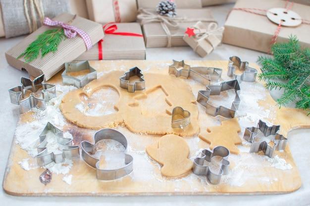 Comida de natal. gengibre de biscoitos de natal em forma de árvores de natal. presentes e thuja. comida caseira. massa e formas.