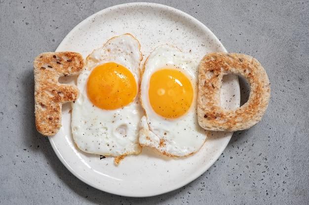 Comida de palavra escrita com letras de torradas ovos fritos